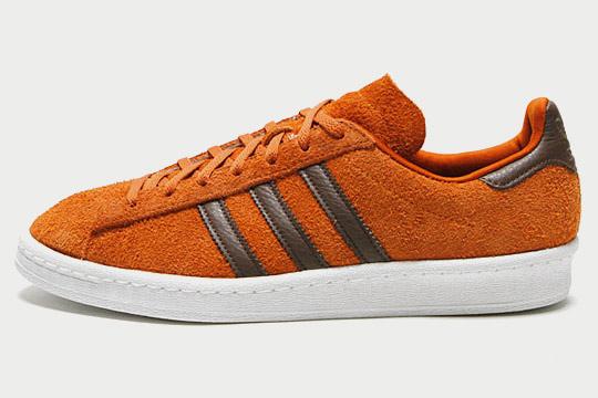 Adidas Campus 80s Game Day. La paire arbore un dessus en daim à poil long burnt orange contrasté par du cuir marron. Les sneakers sortiront le 2