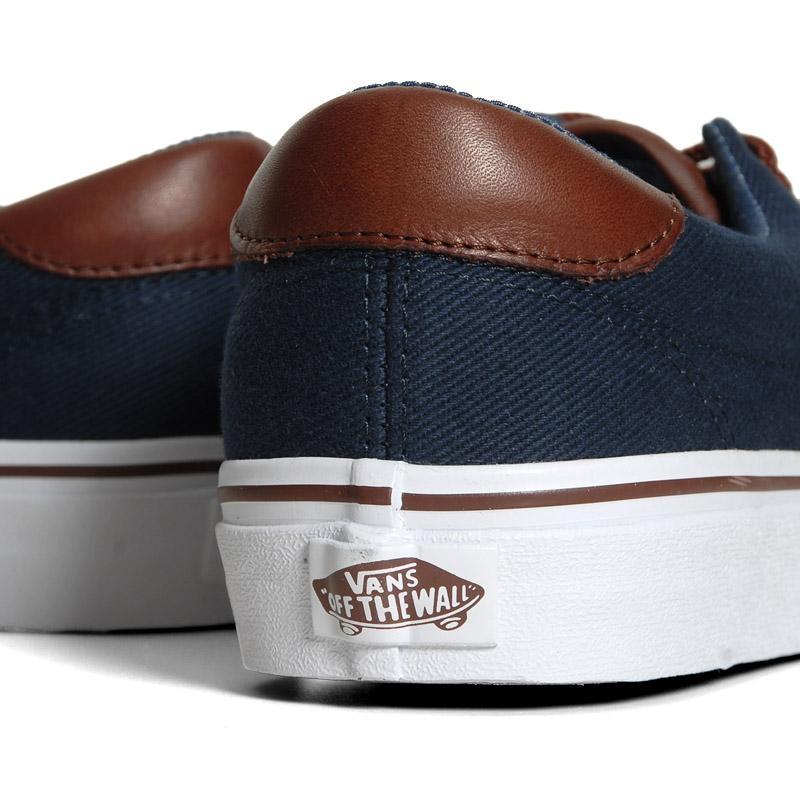 La paire revêt un dessus en canvas bleu foncé combiné à du cuir marron contrastés par une doublure en tissu chambray et une semelle vulcanisée blanche.