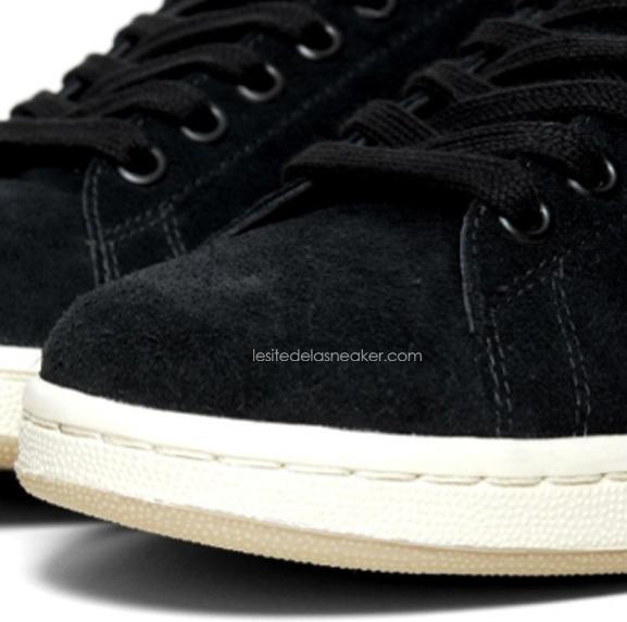 La nouvelle version de l'iconique Adidas Stan Smith arbore un dessus en daim noir contrasté par du cuir marron et par une semelle blanche/beige.