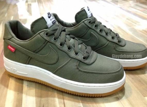 Les sneakers sont conçues en canvas vert olive avec une semelle blanche et  gum, contrastés par le logo rouge supreme et des accents de noir.